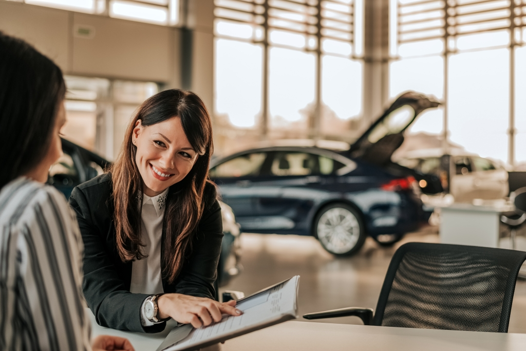 Two women discussing auto finance definitions at a dealership