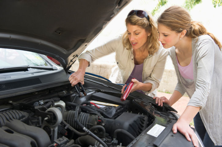 two-women-under-hood-car