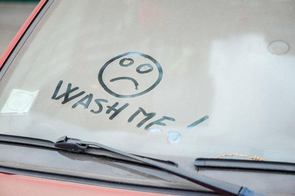 Dirty windshield with Wash Me written in