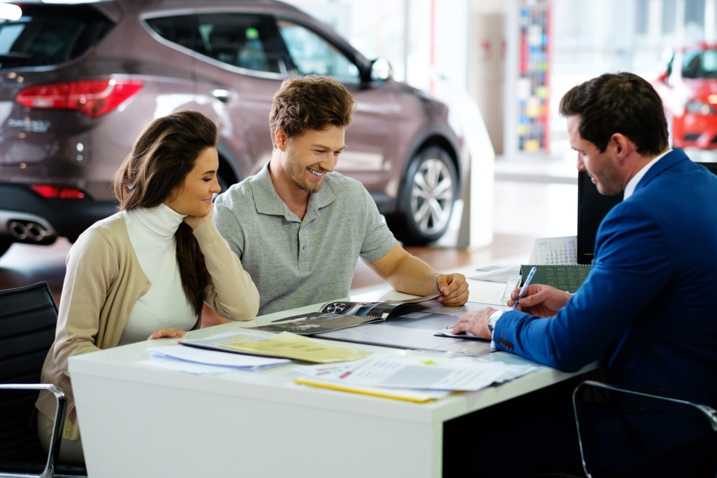 Couple negotiating at car dealership