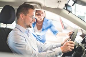 Man behind wheel of new car in dealership