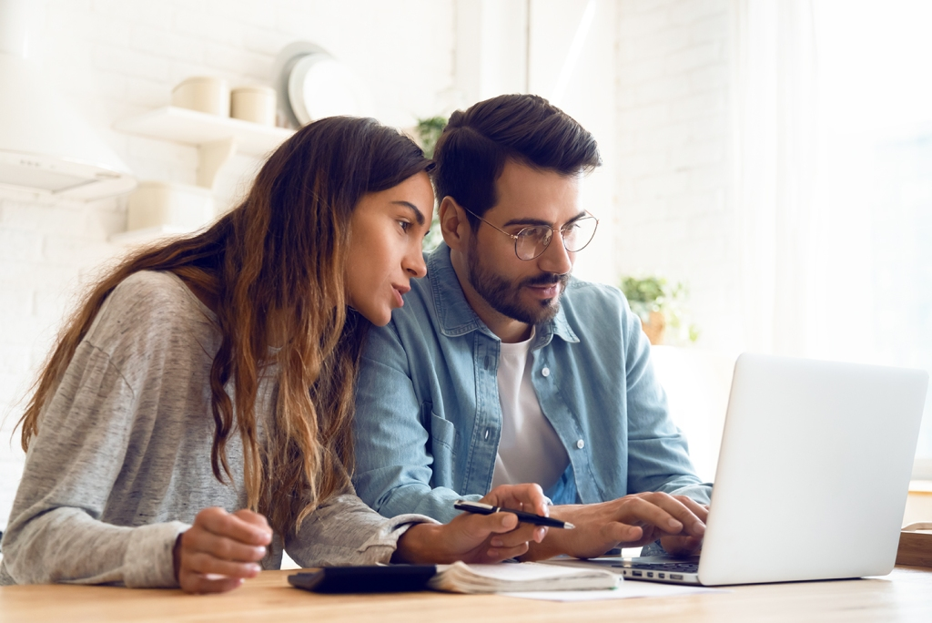 Young couple using computer for auto finances