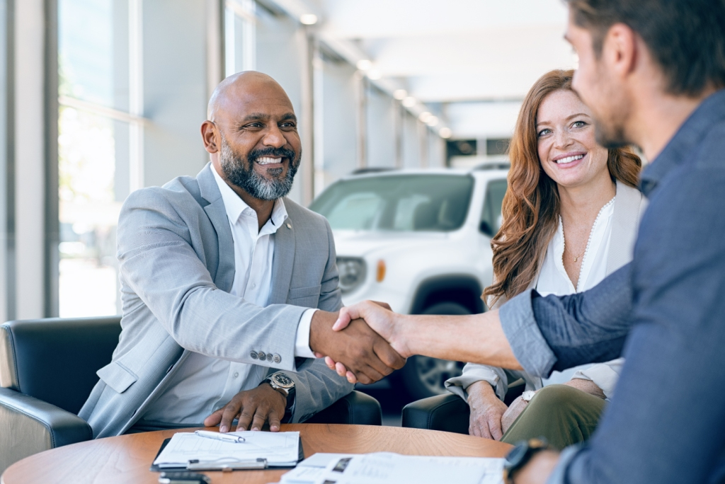 Car buyer shaking hands with dealership representative