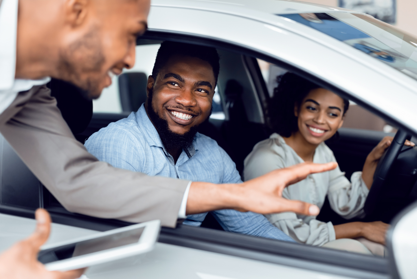 Dealer representative talking to young couple in car